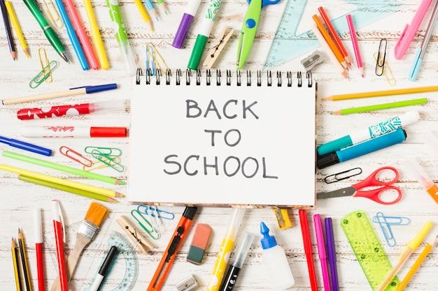 Bloc de notas de regreso a la escuela rodeado de útiles escolares.