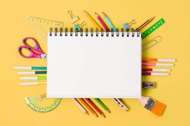 Bloc de notas rodeado de útiles escolares