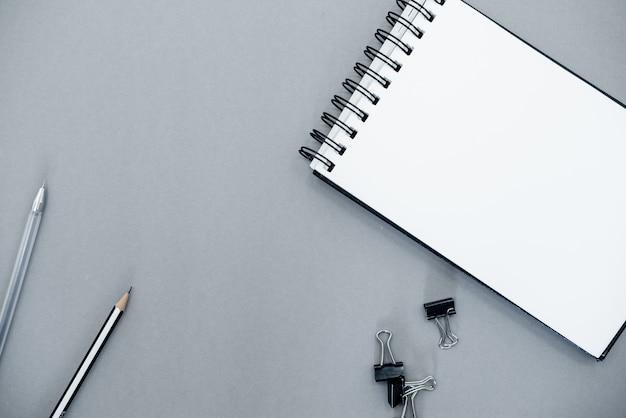 Bloc de notas sobre un fondo abstracto gris con espacio de copia, estilo minimalista.