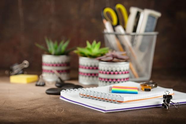 Bloc de notas y suculentas sobre la mesa