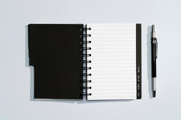 Bloc de notas con tapas negras y bolígrafo