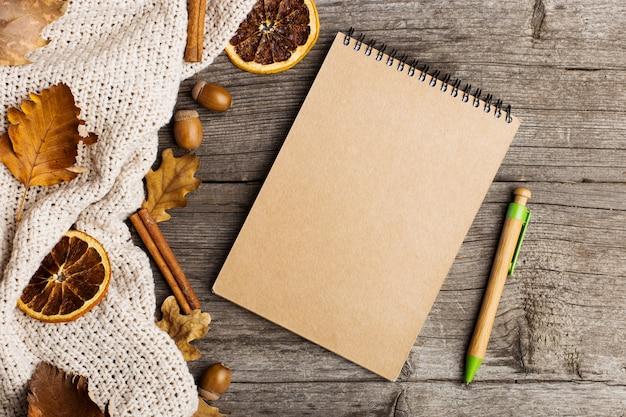 Bloc de notas, tela, hojas y naranja seca.