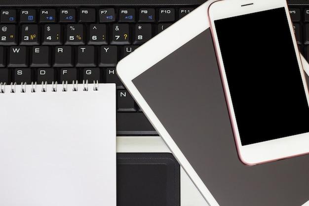 Bloc de notas, teléfono inteligente y tableta en el teclado del ordenador portátil, concepto de negocio