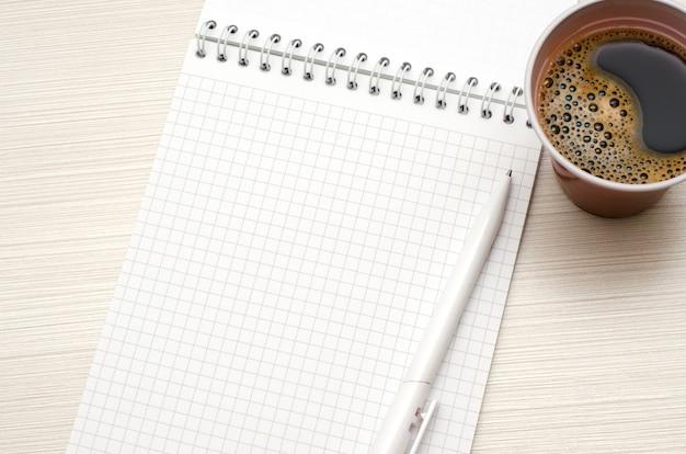 Bloc de notas para el texto. bolígrafo blanco, taza de café