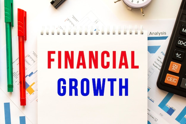 Bloc de notas con el texto crecimiento financiero en un gráfico financiero en color