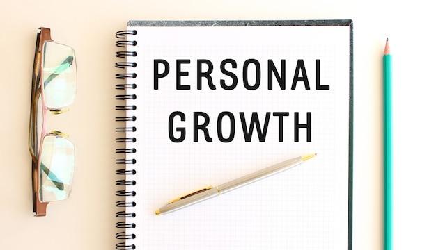 Bloc de notas con texto crecimiento personal sobre un fondo blanco, cerca de gafas y lápiz