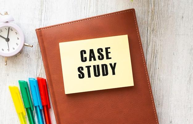 Bloc de notas con texto estudio de caso sobre una superficie blanca, cerca de equipo portátil, calculadora y material de oficina.