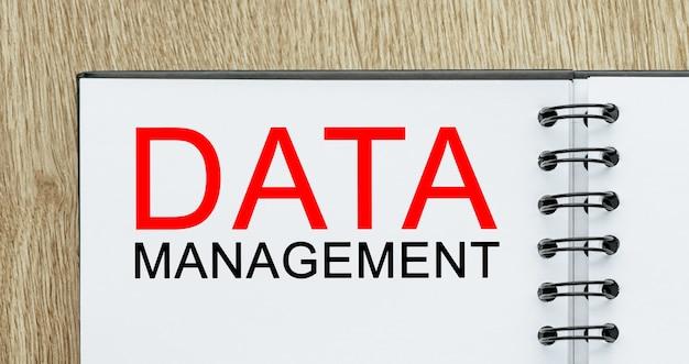 Bloc de notas con texto gestión de datos sobre escritorio de madera