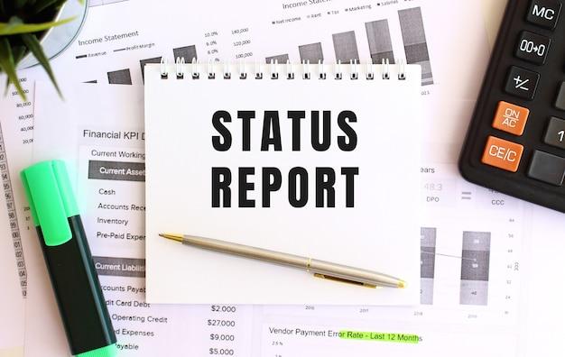 Bloc de notas con texto informe de estado sobre una superficie blanca, cerca de marcador, calculadora y material de oficina.
