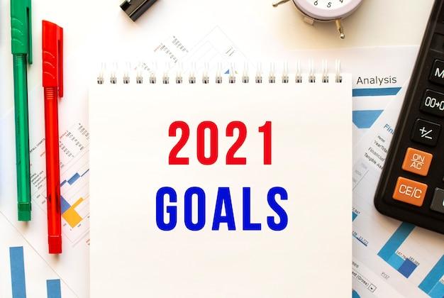 Bloc de notas con el texto objetivos 2021 en un cuadro financiero en color. pluma, calculadora en la mesa de la oficina.