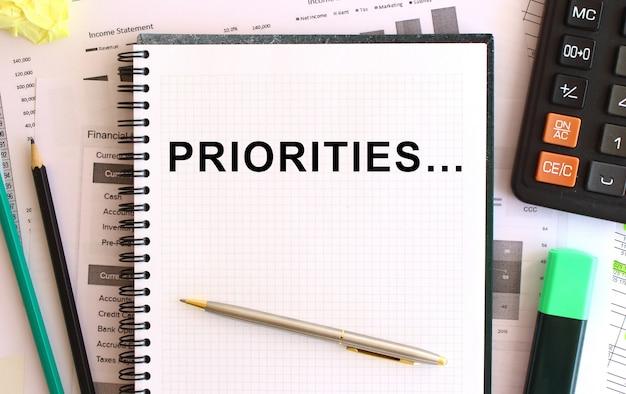 Bloc de notas con texto prioridades cerca de calculadora y útiles de oficina