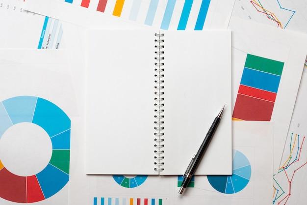 Bloc de notas vacío con lápiz sobre gráficos de negocios, plantilla de investigación o análisis con espacio de copia