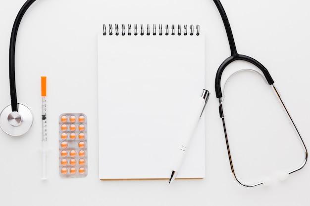 Bloc de notas vacío con pastillas y estetoscopio