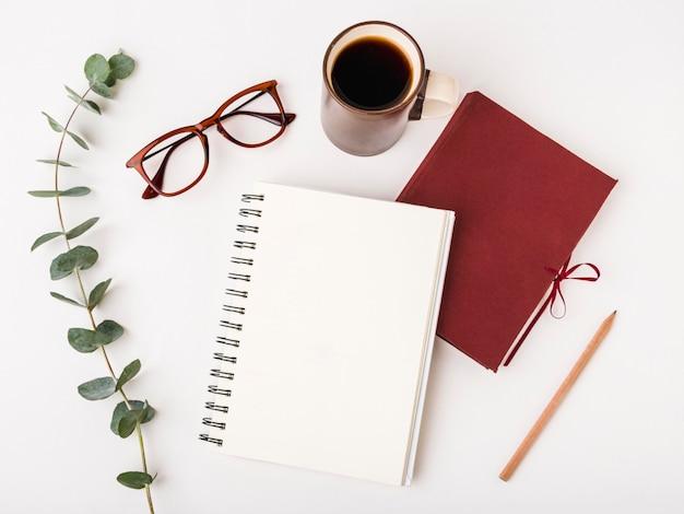 Bloc de notas de vista superior con anteojos y café