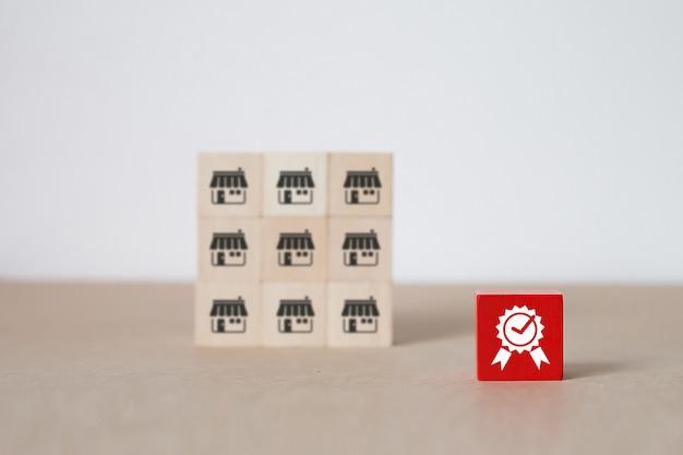 Blog de juguete de madera en forma de cubo apilado con el símbolo de calidad y el fondo de la tienda de iconos de marketing de franquicia.