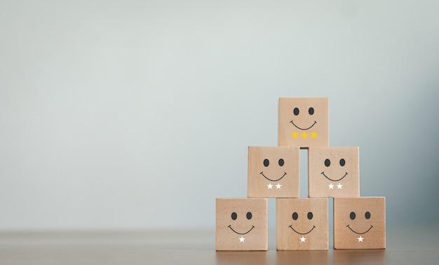Un blog de madera sobre conceptos de evaluación de servicio al cliente el cliente selecciona un icono de cara sonriente