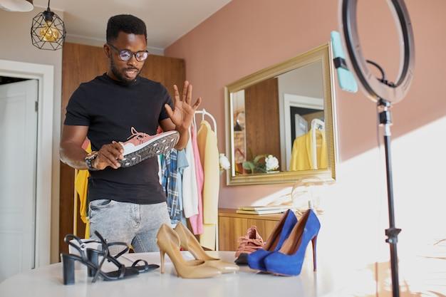 Blogger afro de mente abierta habla a la cámara, muestra ropa y zapatos nuevos