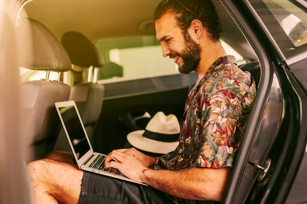 Blogger alegre usando laptop en auto