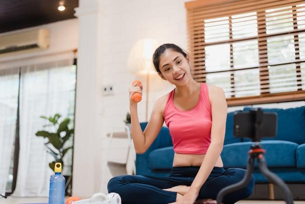 Blogger asiático joven mujer ejercicio y mirando a la cámara en la sala de estar