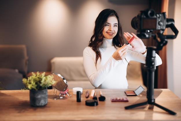 Blogger de belleza bastante femenina filmando un tutorial de rutina de maquillaje diario en la cámara. mujer joven influyente revisión de productos cosméticos de transmisión en vivo en estudio casero. trabajo de vlogger. bricolaje.