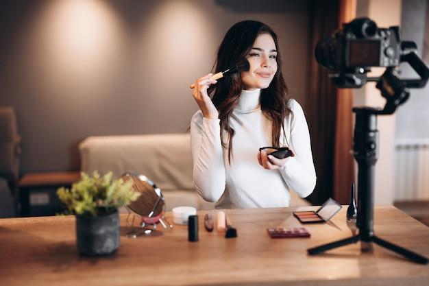 Blogger de belleza bastante femenina filmando un tutorial de rutina de maquillaje diario en la cámara. mujer joven influyente revisión de productos cosméticos de transmisión en vivo en estudio casero. trabajo de vlogger. maquillaje de bricolaje.