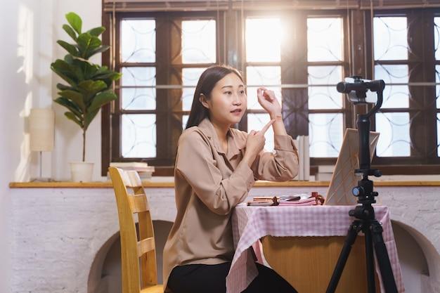 Blogger de belleza femenina asiática transmitió transmisión en vivo para revisar el producto de maquillaje en las redes sociales, influyente joven moderna que demuestra su cosmética diaria mientras habla por la cámara del teléfono inteligente