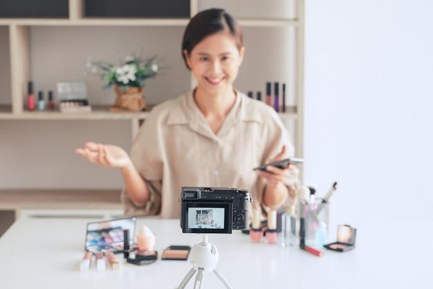 Blogger de belleza grabando video y presentando cosméticos en casa