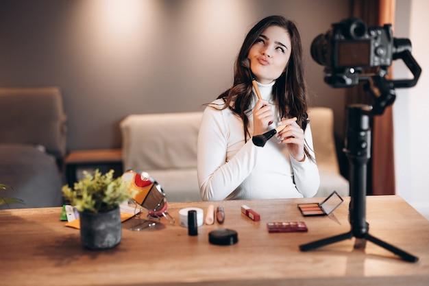 Blogger de belleza mujer agradable filmación tutorial de rutina de maquillaje diario en cámara. mujer joven influyente revisión de productos cosméticos de transmisión en vivo en estudio casero. trabajo de vlogger. maquillaje de bricolaje.