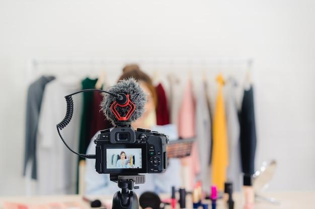 La blogger de belleza presenta cosméticos de belleza en la cámara frontal para grabar video