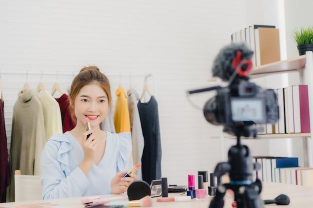 La blogger de belleza presenta cosméticos de belleza mientras está sentada frente a la cámara para grabar video