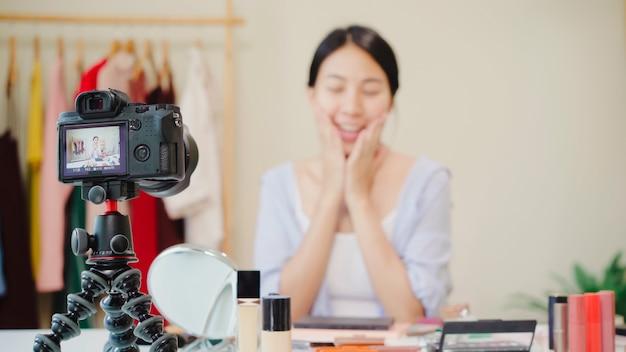 La blogger de belleza presenta cosméticos de belleza que se sientan en la cámara frontal para grabar video.