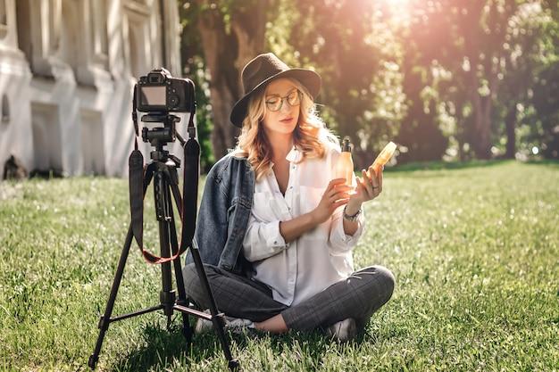 Blogger de chica elegante sentada en la calle sobre la hierba y dispara vlog en la cámara.