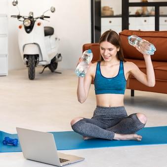 Blogger deportivo sosteniendo botellas de agua frente a la computadora portátil