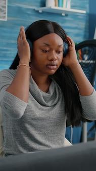 Blogger estudiante afroamericano poniendo auriculares trabajando de forma remota desde casa