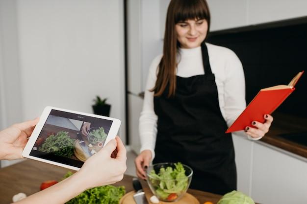 Blogger femenina grabando a sí misma mientras prepara la comida y lee un libro