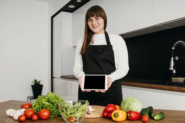 Blogger femenina grabando a sí misma mientras prepara ensalada con tableta