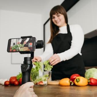 Blogger femenina grabando a sí misma mientras prepara la ensalada