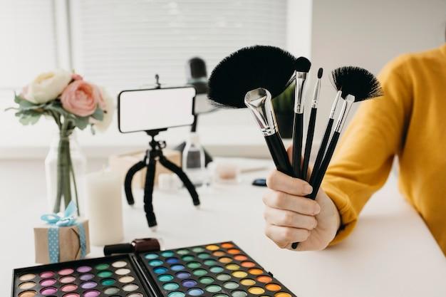 Blogger femenino juego de brochas de maquillaje online con smartphone