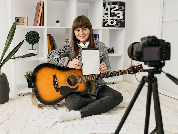 Blogger femenino streaming lecciones de guitarra con cámara en casa