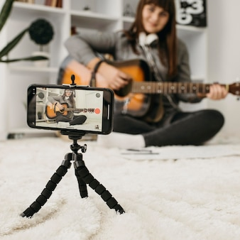 Blogger femenino streaming lecciones de guitarra con cámara smartphone en casa