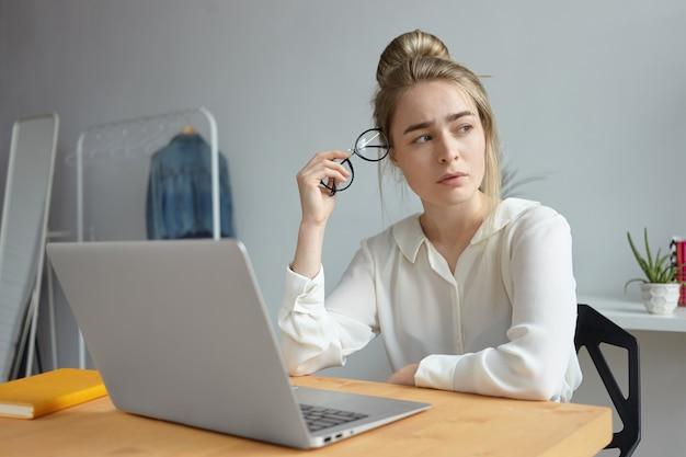 Blogger frustrada y agotada joven vestida con blusa blanca sosteniendo anteojos redondos y mirando a otro lado con expresión preocupada, buscando inspiración, tratando de escribir un artículo para su blog