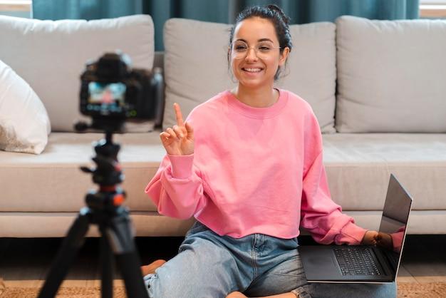 Blogger grabándose a sí misma con gafas sosteniendo una laptop
