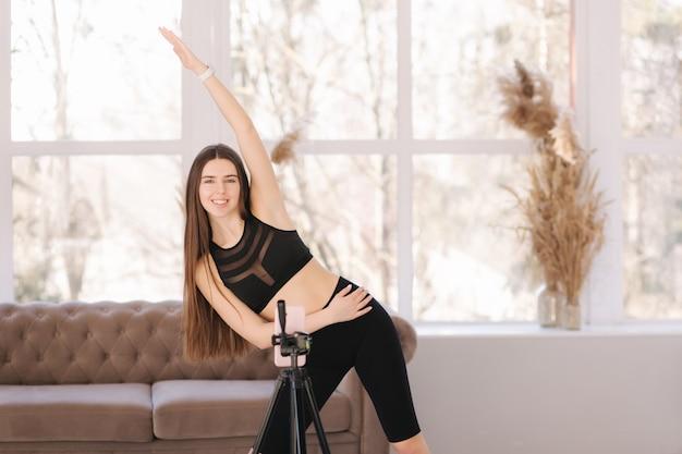 Blogger joven atlética en ropa deportiva negra graba video en el teléfono mientras hace ejercicios en casa en la sala de estar.