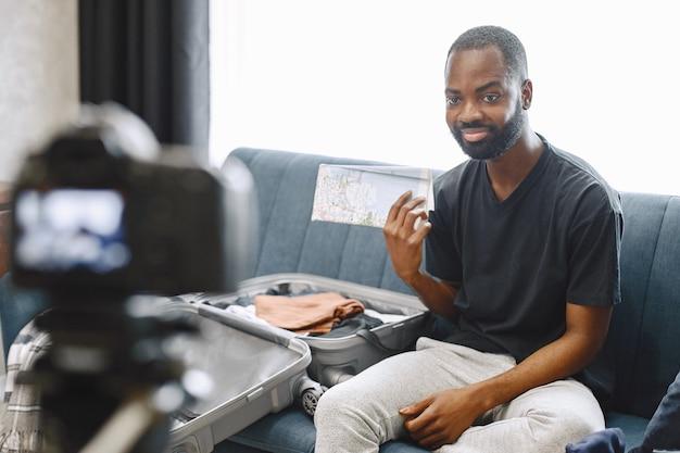 Blogger masculino afroamericano sentado frente a la cámara y grabando un video sobre su equipaje
