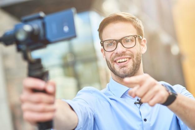 Blogger masculino feliz joven con camisa azul y anteojos sosteniendo un cardán con teléfono inteligente hablando