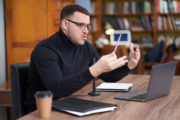 Blogger masculino que transmite desde la biblioteca usando una computadora portátil y un micrófono