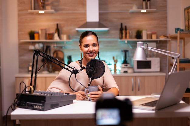 Blogger mirando mientras graba video y hablando por micrófono