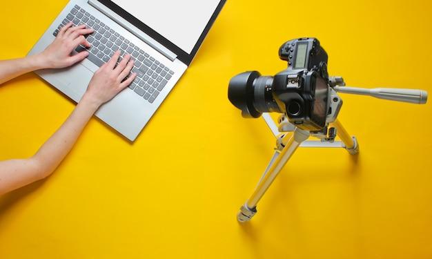 Blogger mujer escribiendo en una computadora portátil, blogueando con una cámara con un trípode sobre una mesa amarilla. technoblogging. revisión del portátil. vista superior