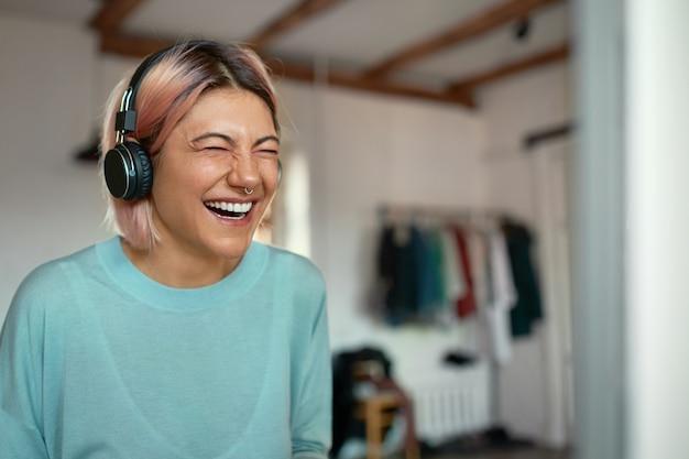Blogger mujer joven positiva alegre con anillo de nariz riendo mientras graba podcast, usando auriculares.