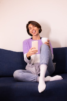 Blogger de mujer linda caucásica en casa en suéter de suéter púrpura cálido tomar selfie en espejo en el teléfono móvil